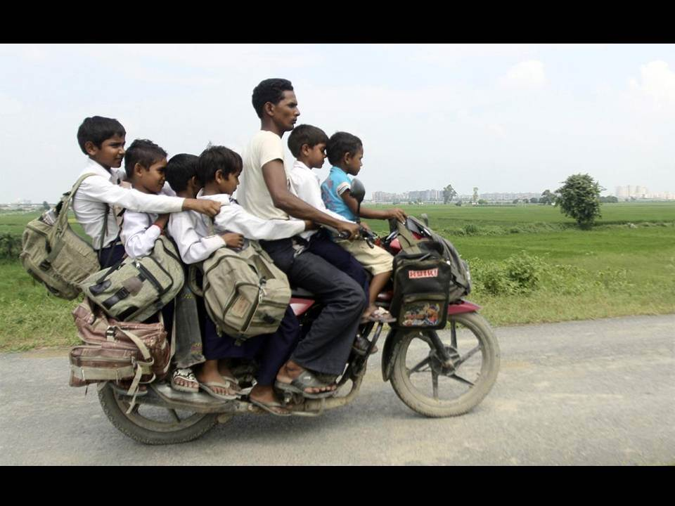Man and Six Children Sharing a Motorcycle