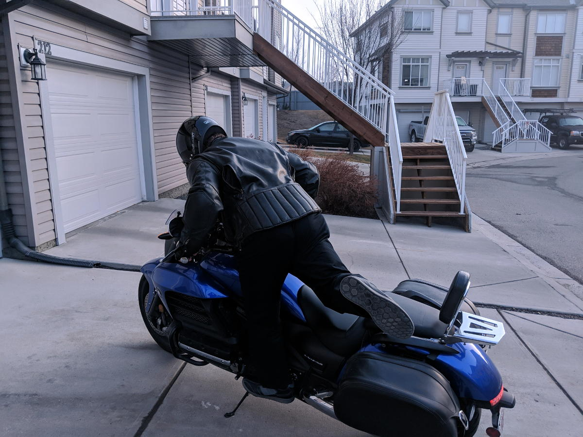 motorcyclist mounting motorcycle using peg as footing front view