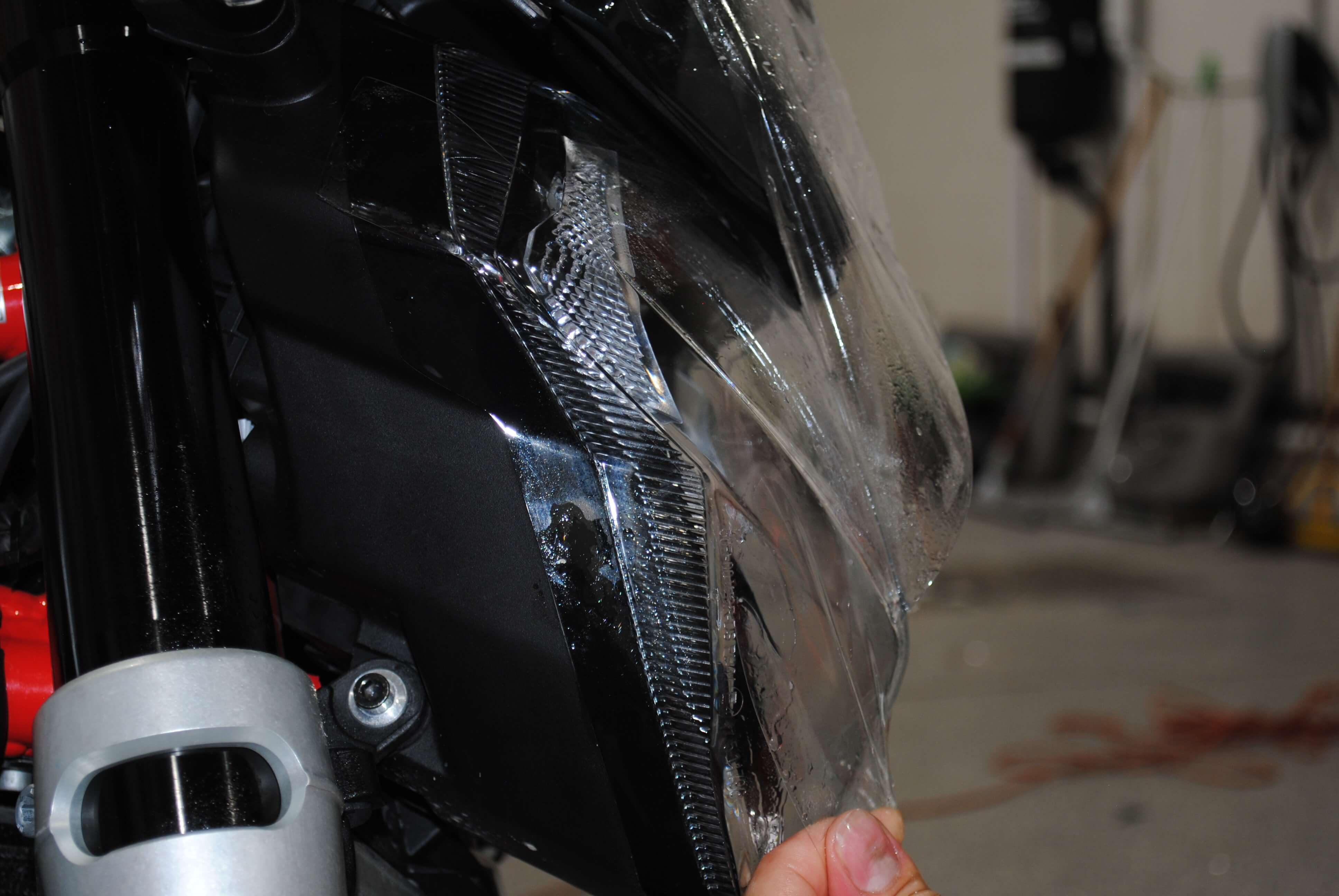 Positioning film in place for installation on Aprilia Shiver