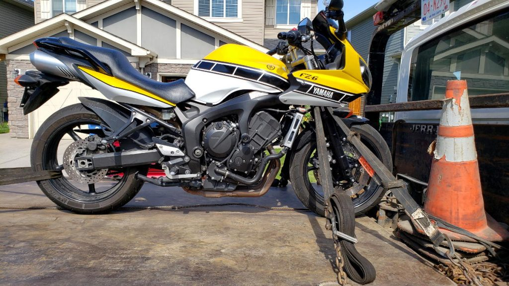Cam's FZ6 secured via four-points on a flatbed tow truck