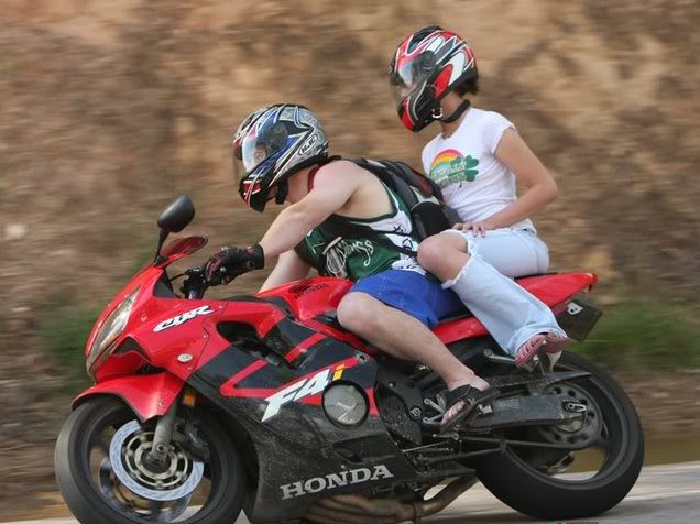 Motorcyclist and passenger riding on red Honda CBR without proper gear