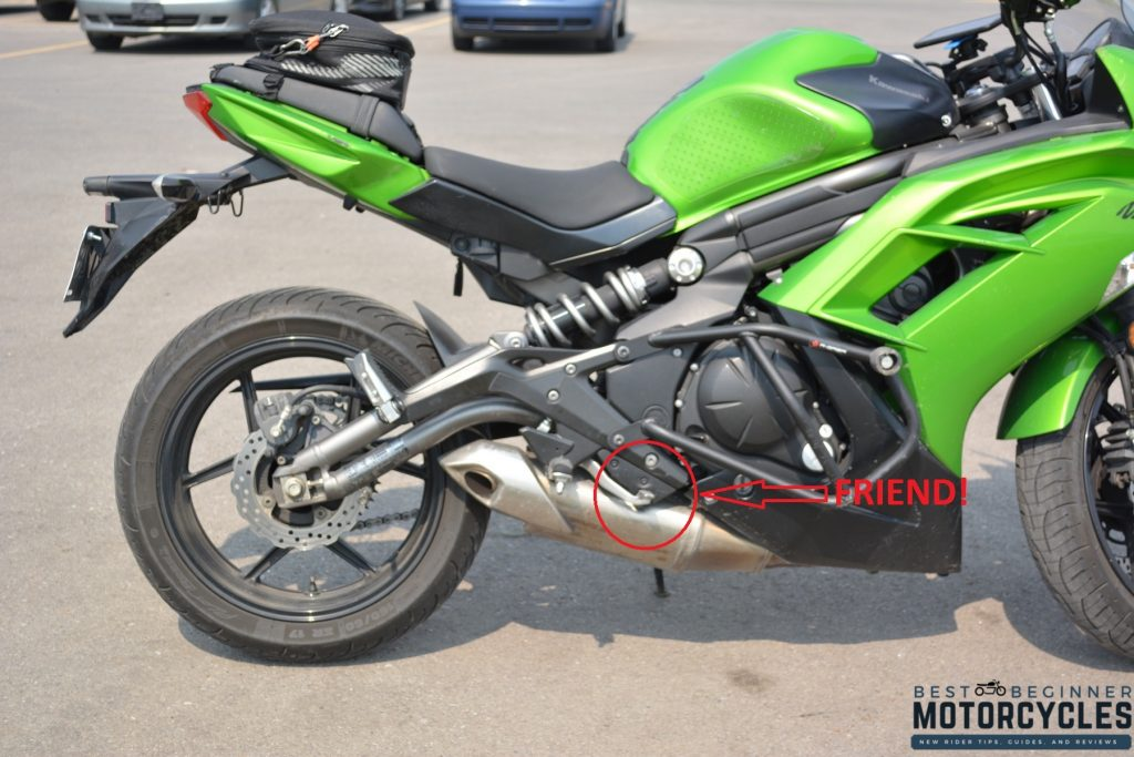 Green Kawasaki Ninja 650 sitting in parking lot with rear brake circled in red and labeled