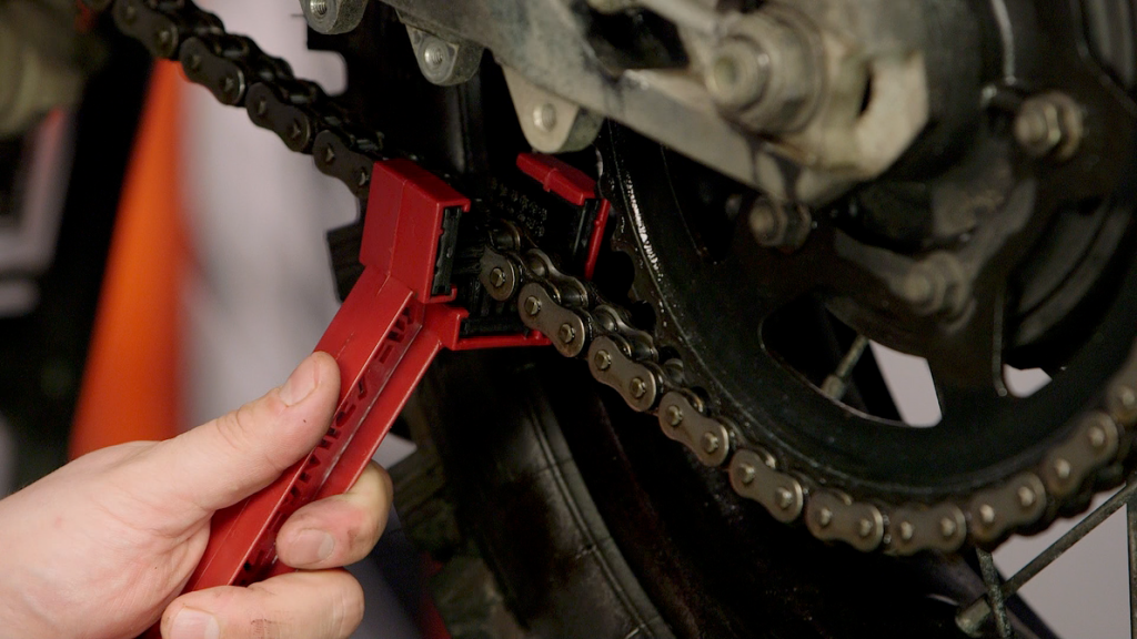 Rider cleaning and lubing a motorcycle chain