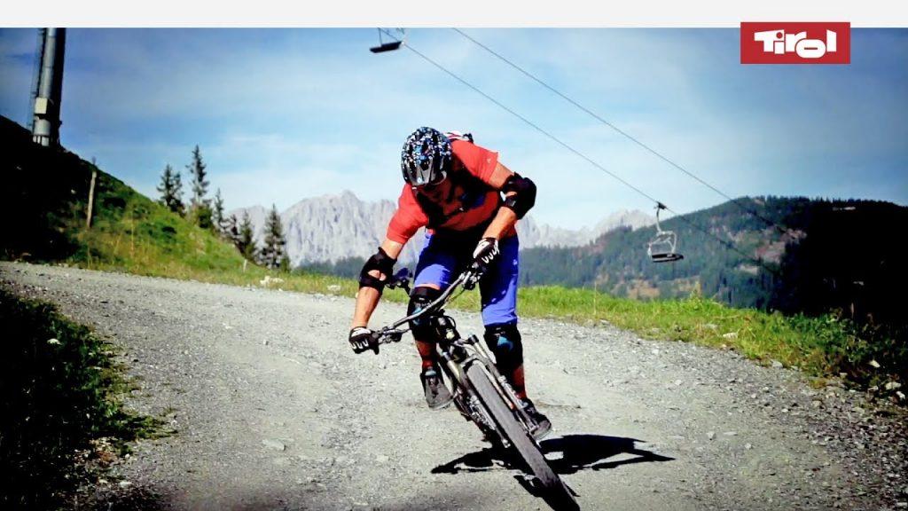 Mountain biker counter-leaning around corner on gravel road