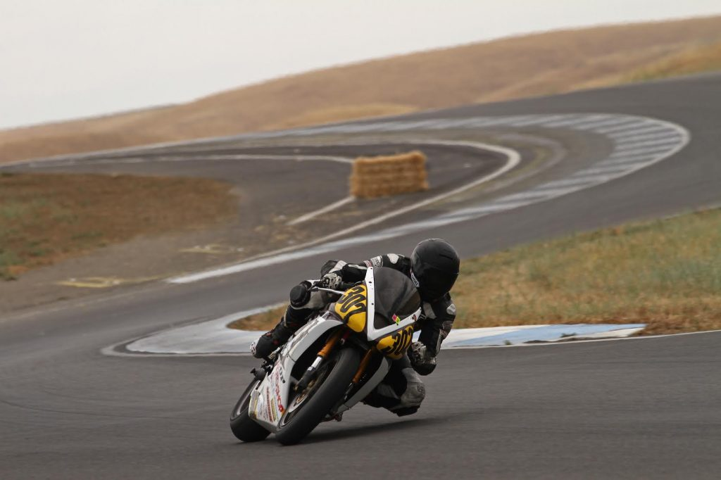 Motorcyclist racing around curve on winding racetrack