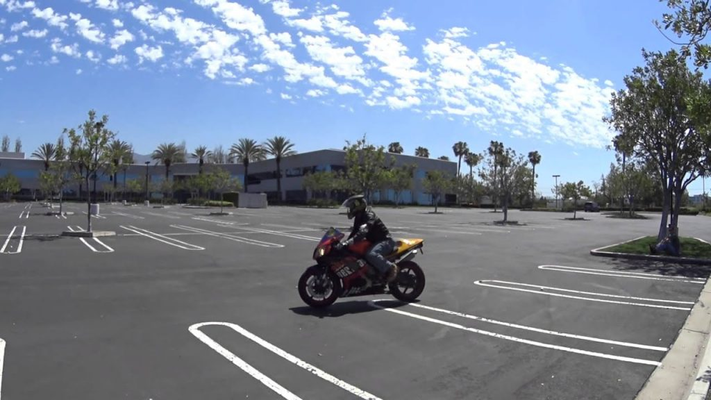 Motorcyclist on bike practicing slow-speed maneuvers in empty parking lot