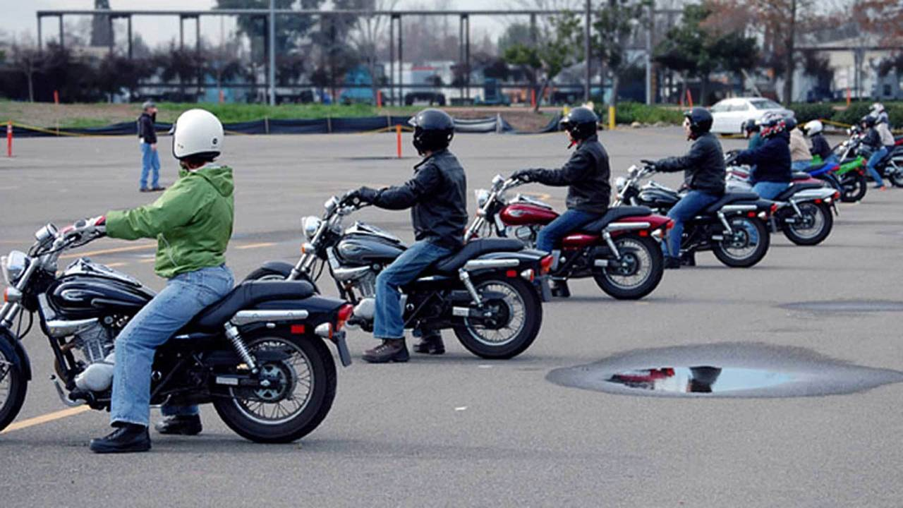 Riders lined up on motorcycles in a parking lot during an MSF class